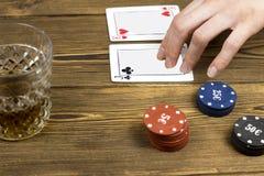 Рука спирта карточки обломоков покера, деревянная предпосылка, играя в азартные игры стоковая фотография