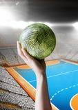 Рука спортсмена держа шарик против предпосылки стадиона Стоковая Фотография RF