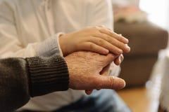 Рука старого человека держа руку ребенк Стоковая Фотография RF