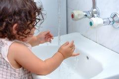 Рука стирки ребенка с водой Для того чтобы держать вирус гриппа на заливе, помойте ваши руки с мылом и водой несколько времен ден стоковые изображения