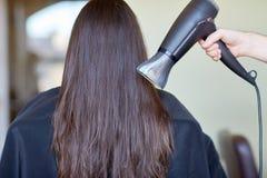 Рука стилизатора с вентилятором сушит волосы женщины на салоне Стоковое Изображение RF