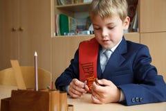 рука стола мальчика его школьная форма пер Стоковое фото RF