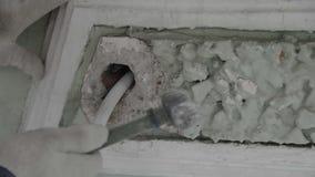Рука строя работника держит небольшой молоток и ударяет крошечную часть стены фасада видеоматериал
