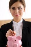 Рука счастливой усмехаясь коммерсантки кладя деньги штыря в пинк Стоковые Фотографии RF