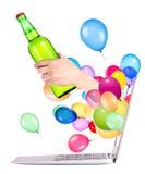 Рука с бутылкой пива и компьтер-книжки Стоковая Фотография RF