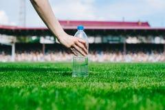 Рука с бутылкой с водой на стадионе стоковые фотографии rf