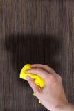 Рука с ветошью для того чтобы запылиться деревянная мебель стоковая фотография rf