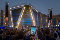 Рука с видео записи smartphone/фото на концерте живой музыки, силуэтами толпы перед ярким этапом освещает стоковые изображения