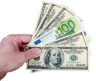 Рука с долларом и евро на белизне стоковое изображение rf