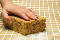 Рука с желтой губкой Стоковые Фото