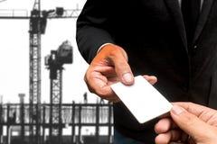 Рука с карточкой имени с краном конструкции в предпосылке стоковые фото