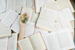 Рука с компасом среди много книг стоковое фото rf