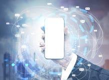 Рука с насмешкой вверх по smartphone, голубому городу Стоковая Фотография RF