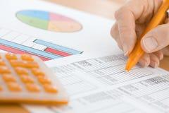 Рука с оранжевой ручкой и калькулятор проверяя диаграммы электронной таблицы Стоковые Фотографии RF