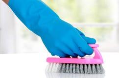 Рука с перчаткой используя щетку чистки, который нужно очистить вверх стоковое фото