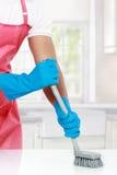 Рука с перчаткой используя щетку чистки, который нужно очистить вверх стоковые фото
