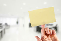 Рука с пустым липким примечанием на пальце в офисе Стоковая Фотография RF