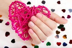 Рука с розовым штейном делать ногти держа сердце Стоковое Изображение RF