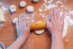 Рука с роликом и тестом большого пальца руки на деревянном столе, Стоковые Изображения