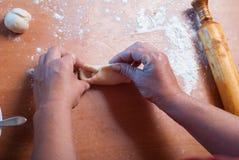 Рука с роликом и тестом большого пальца руки на деревянном столе, Стоковые Изображения RF