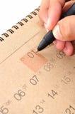 Рука с ручкой принимает примечание в календарь стоковая фотография rf