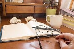 Рука с стеклянной ручкой на тетради скомкала бумагу Стоковая Фотография