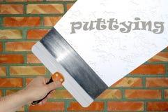 Рука с стеной выстучанной шпателем Стоковая Фотография RF