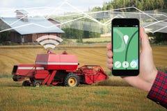 Рука с телефоном На интерфейсе управлением экрана собственной личности управляя жаткой зернокомбайна стоковое фото rf