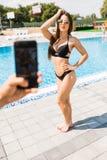 Рука с телефоном принимает фото женщины красоты сексуальной в swimwear около бассейна Время для фото лета взрослые молодые стоковое изображение rf