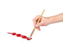 Рука с щеткой рисует красную линию стоковое изображение