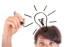 Рука с электрической лампочкой чертежа ручки Стоковые Изображения
