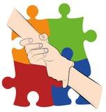 Рука удерживания руки на предпосылке покрашенных головоломок Символ аутизма День аутизма мира также вектор иллюстрации притяжки c стоковое изображение rf