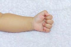 рука удавки младенца на белых пеленках Стоковое Изображение RF