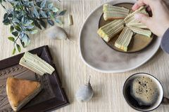 """Рука хватает кусок мульти-наслоенного вызванного тортом """"законно рожденного lapis """"или """"spekkoek """"от Индонезии стоковое фото rf"""