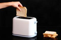 рука хлеба кладя к тостеру Стоковые Фото
