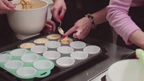 Рука хлебопека десерта кладет тесто в чашки пергаментной бумаги булочек на поднос выпечки сток-видео