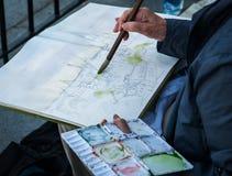 Рука художника при paintbrush крася изображение aquarelle Стоковые Изображения