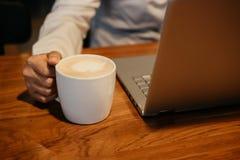рука чашки владением бизнесмена с кофе и другая рука печатая o Стоковые Фотографии RF