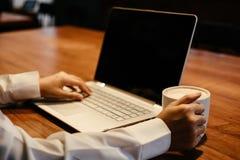 рука чашки владением бизнесмена с кофе и другая рука печатая o Стоковое фото RF