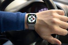 Рука человека в автомобиле с серией 4 дозора Яблока стоковая фотография