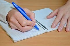 Рука человека в белой рубашке пишет текст с голубой ручкой в тетради со спиралью на деревянном столе стоковое фото