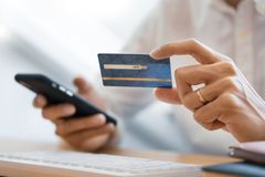 Рука человека в случайной рубашке оплачивая с кредитной карточкой и используя умный телефон для онлайн покупок делая заказы через стоковая фотография rf