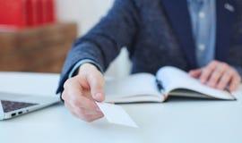 Рука человека давая визитную карточку в офисе Человек показывая пустую визитную карточку Дизайн насмешки поднимающий вверх Стоковые Изображения