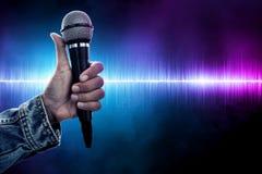 Рука человека держа беспроводной микрофон стоковые изображения rf