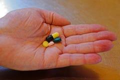 Рука человека держа выбор таблеток стоковые изображения