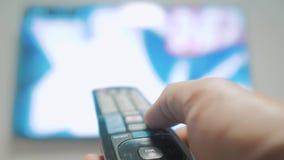 Рука человека держа дистанционное управление ТВ и повернуть умное ТВ заниматься серфингом канала Конец вверх укомплектовывает лич видеоматериал