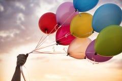 Рука человека держа красочные воздушные шары и красивый заход солнца Воздушные шары вечеринки по случаю дня рождения стоковое фото rf