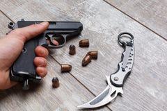 Рука человека держа пистолет, рядом с патроны и нож Стоковые Фотографии RF
