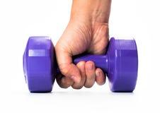 Рука человека держа фиолетовую гантель изолированный на белой предпосылке конец вверх concept healthy lifestyle стоковые фото