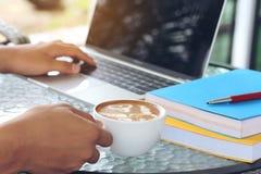 Рука человека держа чашки искусства latte с использовать ноутбук внутри стоковое фото